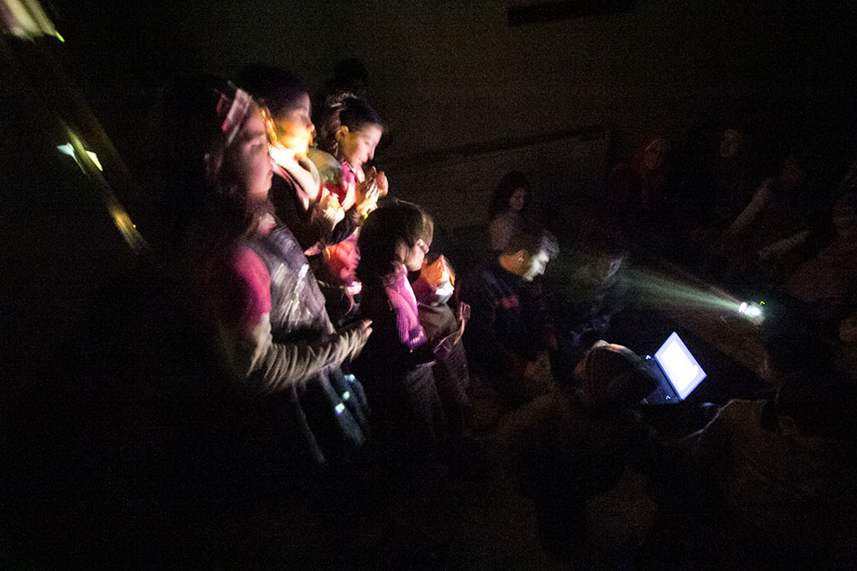 """Bild von Kindern, die in einem kleinen Schutzraum singen, während ein Flugzeug über sie hinwegfliegt / """"The shadow vocals """", Syrien. Foto: Giath Taha"""