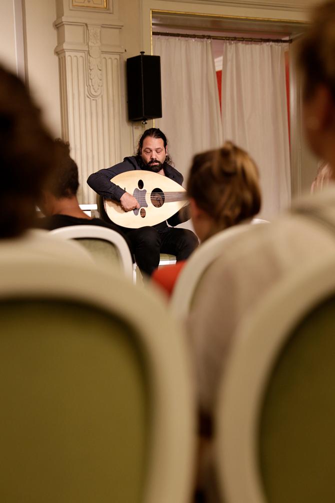 Wassim Mukdad ist einer der renommiertesten Oud-Spieler aus Syrien. Er improvisiert fünf Stücke und versinkt dabei so sehr in seiner Musik, dass die Zuhörer*innen mitsinken. Als Annika Reich ihn fragt, wann er bei seinen zahlreichen Projekten und Engagements überhaupt noch zum Schlafen kommt, antwortet er: Im Zug.