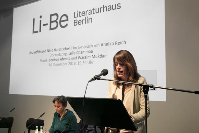 """Janika Gelinek vom Literaturhaus Berlin begrüßt das Publikum und heißt die Autorinnen Lina Atfah und Nino Haratischwili zu ihrer ersten gemeinsamen Lesung willkommen. Im Hintergrund spielt das Video der Weiter Schreiben Premiere des Buchs """"Dein Herz verlässt keinen Ort, an dem es hängt"""