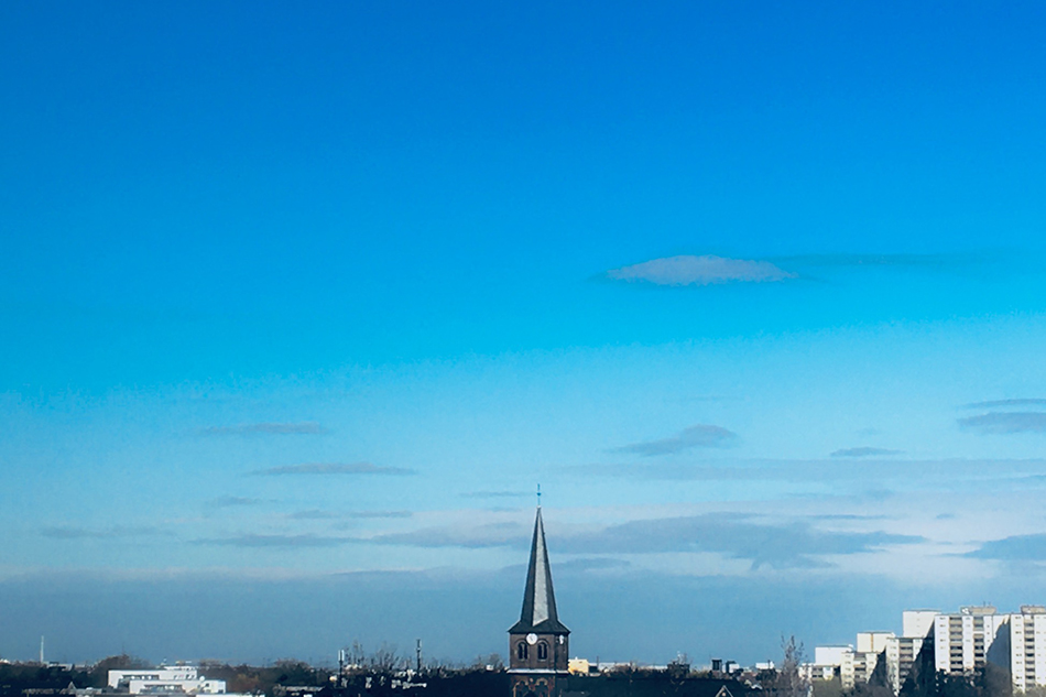 Blick zum Horizont mit Kirchturm und Himmel. (W)Ortwechseln. © Pegah Ahmadi